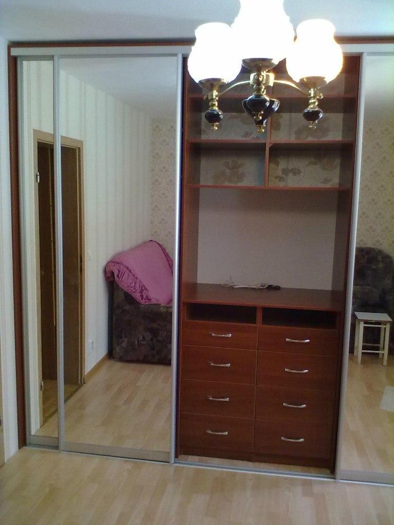 В центре шкафа отдел с выдвижными ящиками, полками и местом под телевизор