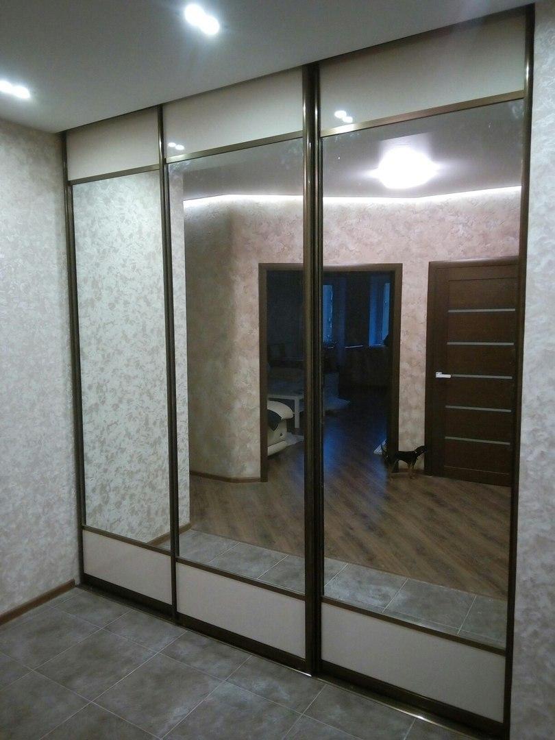 Зеркальные двери шкафа изготовлены с небольшими вставками внизу и вверху
