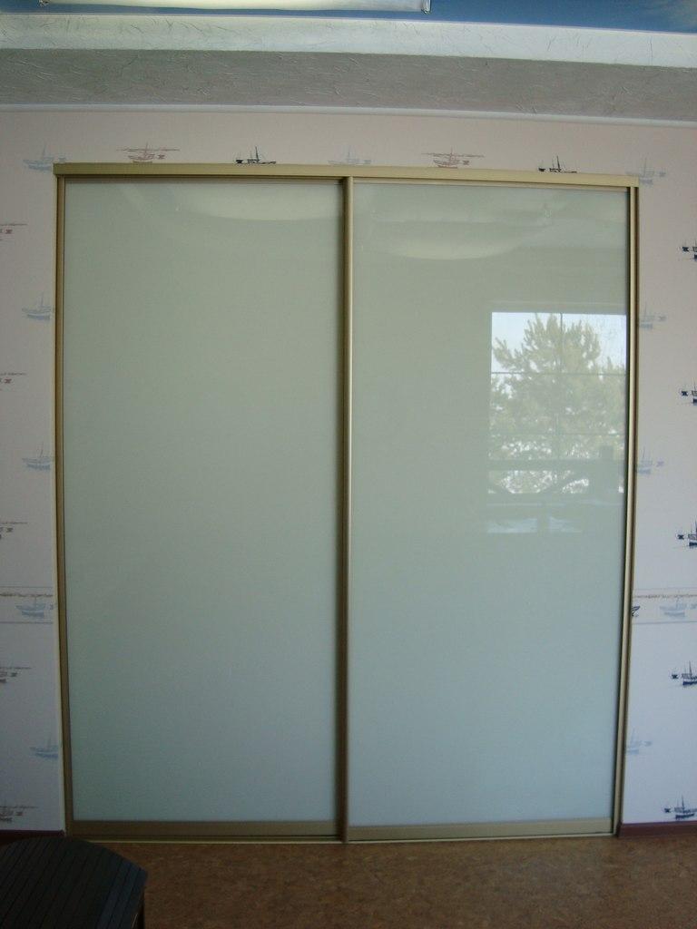 Белые лаконичные двери из стекла в позолоченом профиле
